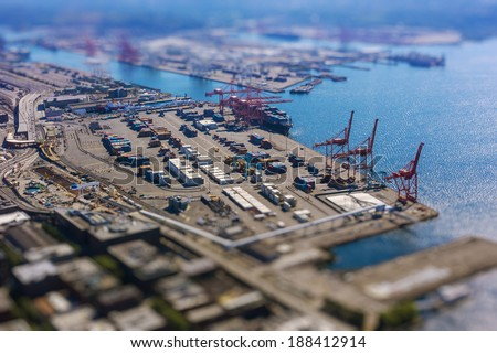 Tilt shift of shipping port with containers and loading transport ship with cargo - stock photo