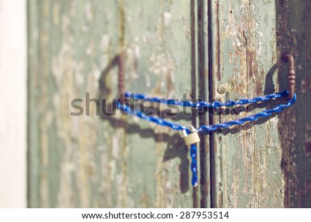 Tilt shift photo of Door with chain and blue lock - stock photo