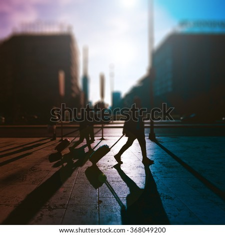 Tilt shift vintage filtered of people walking outdoor on the sidewalk in the city with their luggage - commute, work, business concept - stock photo