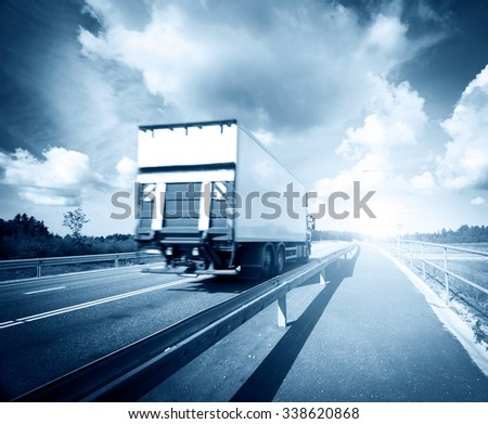 tilt truck moving on the asphalt road - stock photo