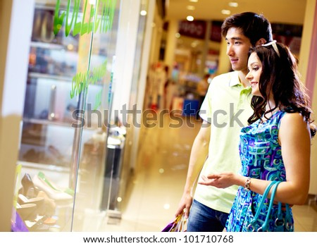 Tilt up of young couple standing in front of the shop window and looking at the merchandise