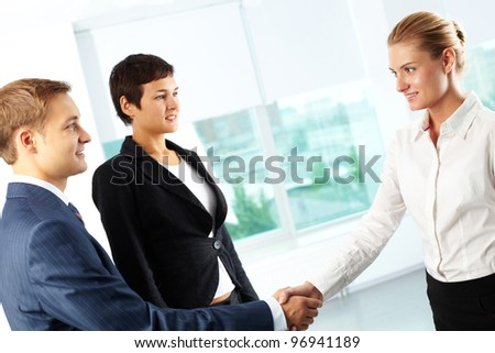 Tilt up shot of business people shaking hands looking positively