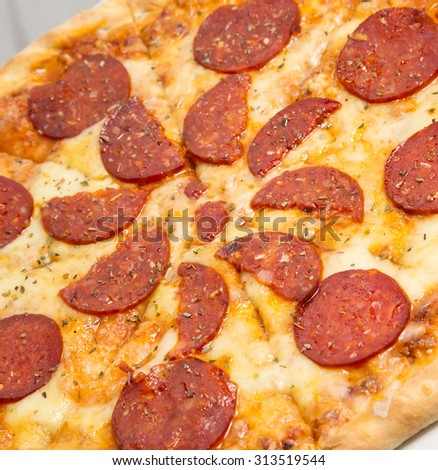 Tilted close up shot of Pepperoni pizza delivered to your door sprinkled with oregano - stock photo