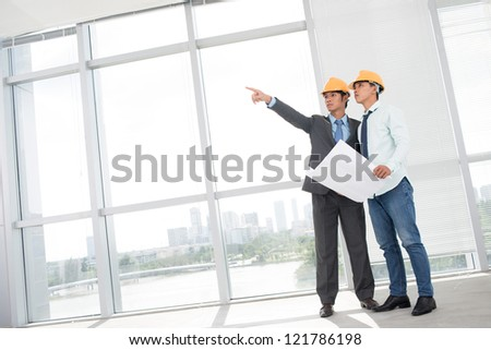 Tilted image of two supervisors comparing blueprint with actual building interior - stock photo
