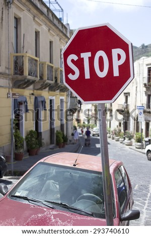 Tilted Stop Sign in focus, blurred street with people walking in the background - stock photo