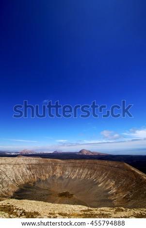 timanfaya vulcanic  rock stone sky  hill and summer in los volcanes lanzarote spain plant flower bush - stock photo