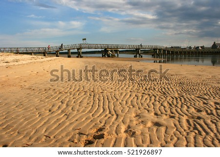 Timber built footbridge from the mainland to the sandbar at Kinloss North East Scotland at low tide and showing the ripples left in the sand by the ebb tide.
