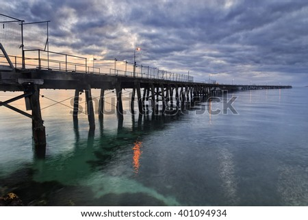 Timber historic jetty for fishing and recreation in sea port town of Esperance, Western Australia, at sunrise. Bended jetty is a local landmark.