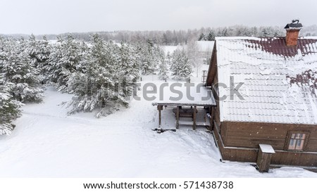 Timber rural house with summer porch is in winter forest. Russian countryside, Russia
