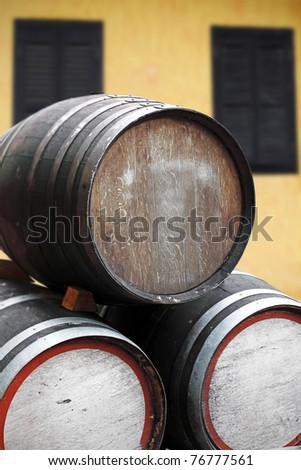 Timber storage barrels with blank space for copyspace text stack on its side in front of a rustic tavern.