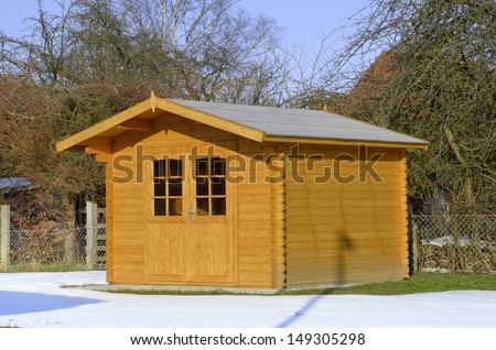 Timbered garden shed in snow - stock photo