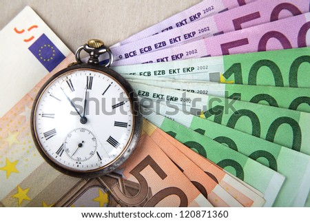 Time and Money concept image. Euro banknotes with vintage watch. - stock photo