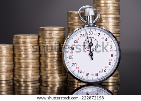 Time and money growth over black background - stock photo