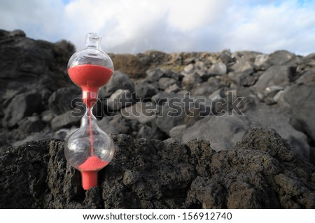 Time Concept - Hourglass Abandoned on the Volcanic Rocks - stock photo