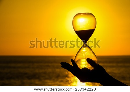 Time Concept Hourglass and Sun Setting on the Atlantic Ocean - stock photo