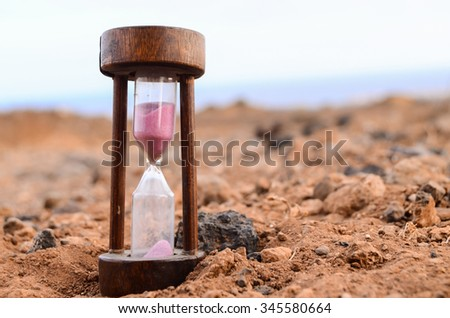 Time Concept Hourglass on the Rock Desert - stock photo