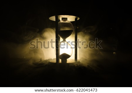 Time concept. Silhouette of Hourglass clock and smoke on dark background with hot yellow orange lighting, or symbols of time with copy space, sandglass or sand clock on chessboard