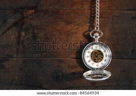 Time concept. Stylish pocket watch hanging with chain against old wooden background - stock photo