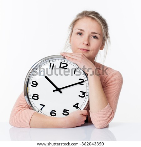 time concept - thinking beautiful young blond woman embracing a clock, holding her teenager past tight, white background