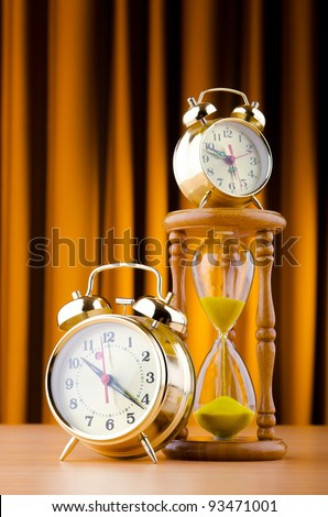 Time concept with alarm clock and hourglass
