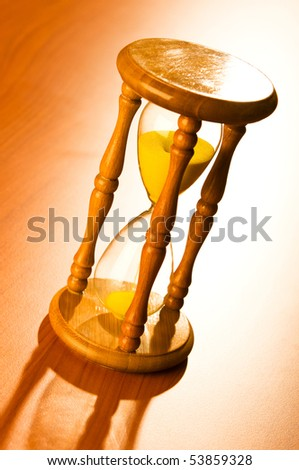 Time concept with hourglass on wooden background - stock photo