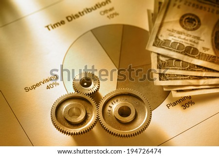 Time distribution diagram with mechanical wrench and money in toning - stock photo