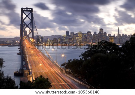 Time exposure image of traffic on the Bay Bridge from Treasure Island with San Francisco in the background at sunset. - stock photo