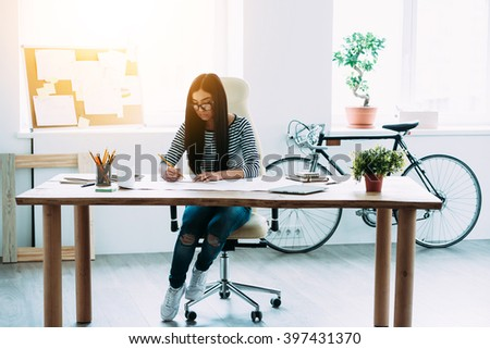 Time flies fast when you work with blueprints. Full length of young beautiful Asian woman drafting at blueprints while sitting at her working place - stock photo