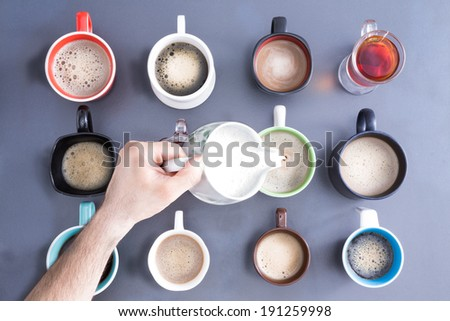 Time for a coffee break for mass concept, with a neat line up of different mugs and glasses containing freshly brewed coffee and tea for a daily dose of caffeine to energize your day, view from above - stock photo