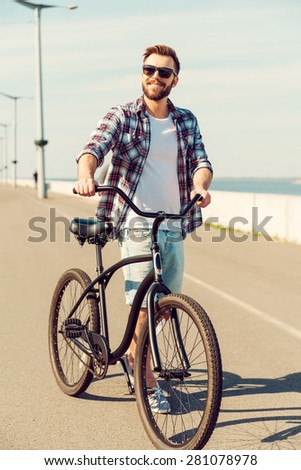 Time for a cycle. Handsome young smiling man walking along a road with his bicycle   - stock photo