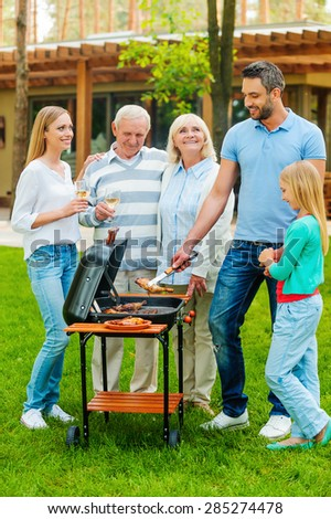 Time for barbeque. Full length of happy family barbecuing meat on grill outdoors - stock photo