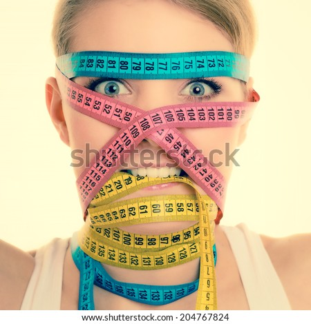 Time for diet slimming weight loss concept. Sport fit fitness woman with many measure tapes around her head. Obsessed girl by your body. vintage retro instagram filter - stock photo