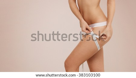 Time for diet slimming weight loss. Fitness woman fit girl in lingerie with measure tape measuring her thigh. - stock photo