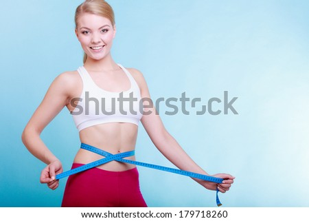 Time for diet slimming weight loss. Health care and healthy nutrition. Young fitness woman fit girl with measure tape measuring her waistline on blue  - stock photo