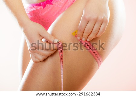 Time for diet slimming weight loss. Health care and healthy nutrition. Young fitness woman fit girl with measure tape measuring her thigh, closeup