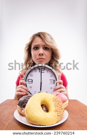 Time for diet slimming. Young beautiful woman with clock keeps from eating doughnuts after 6 pm - weight loss concept, close-up portrait selected focus isolated on a white background - stock photo