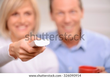 Time for entertainment. Selective focus of remote control in hands of charming positive adult woman holding it and watching TV with her husband - stock photo