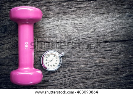 Time for exercising pocket watch and dumbbell on wooden background. - stock photo