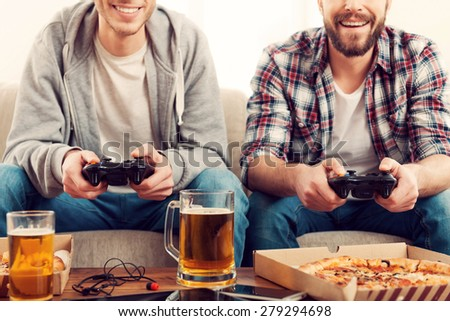Time for games. Cropped image of two young men playing video games while sitting on sofa - stock photo