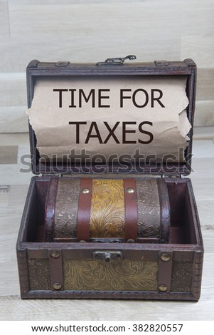 time for taxes is written on the Brown torn paper in the treasure box. Tax Refund