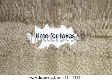 time for taxes written under torn burlap. - stock photo