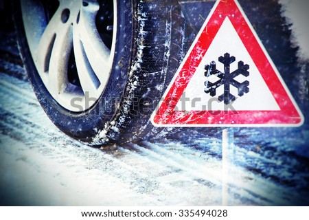 Time for winter tires - tire in winter with traffic sign - stock photo