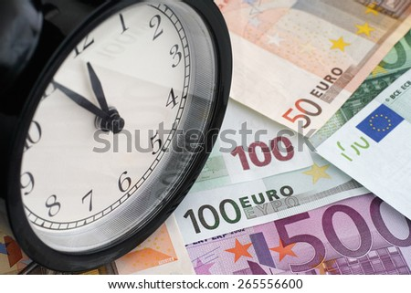Time is money. Alarm clock and euro banknotes. - stock photo
