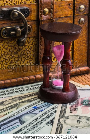 Time is money. An hourglass on the background of money - stock photo