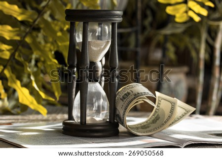 Time is money business philosophy. Hourglass and one hundred dollar bills on financial pages of broadsheet newspaper. - stock photo