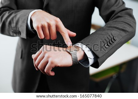 Time is money. Businessman pointing on watch. Business concept - stock photo