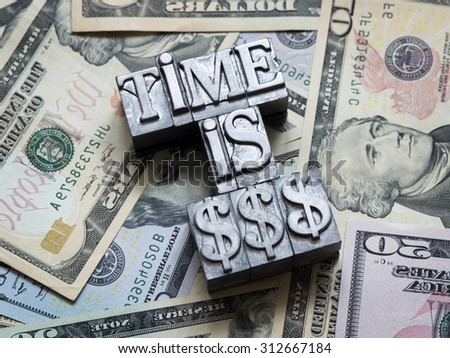time is money concept made from metallic letterpress type on heap of US dollars - stock photo