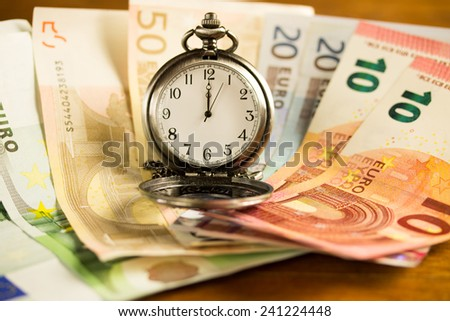 time is money concept with euros and a pocket watch - stock photo