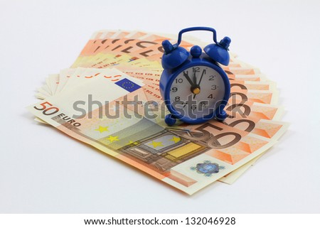 Time is money concept with miniature clock on banknotes