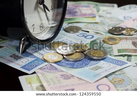 Time is money concept with polish coins and banknotes - stock photo